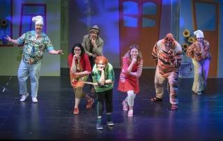Seitsemän näyttelijää poseeraavat rooliasuissaan näyttämöllä